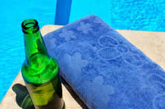 Beer and towel near the pool Stock Photo
