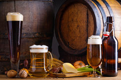 Beer and traditional food. Cellar still life with beer, traditional food and barrels Stock Photos
