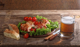 Beer in a transparent mug and chicken beaters in bacon submitted. With greens, bread and tomatoes stock images
