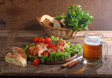 Beer in a transparent mug and chicken beaters in bacon submitted. With greens, bread and tomatoes royalty free stock photography