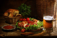 Beer in a transparent mug and chicken beaters in bacon submitted. With greens, bread and tomatoes stock photos