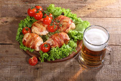 Beer in a transparent mug and chicken beaters in bacon submitted. With greens, bread and tomatoes on a wooden table stock photos