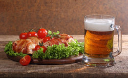 Beer in a transparent mug and chicken beaters in bacon submitted. With greens, bread and tomatoes on a wooden table stock photography