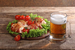 Beer in a transparent mug and chicken beaters in bacon on a wood. En table royalty free stock photos
