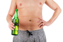 Beer tummy. Close up picture of a young man`s belly holding a beer Royalty Free Stock Image