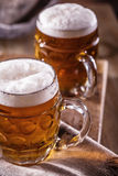 Beer. Two cold beers. Draft beer. Draft ale. Golden beer. Golden ale. Two gold beer with froth on top. Stock Photos