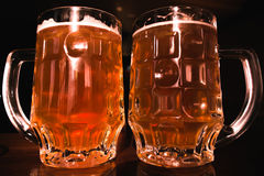 Beer. Two cold beers. Draft beer. Draft ale. Golden beer. Golden ale. Two gold beer with froth on top. Stock Image