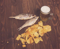 Beer, two fishes and chips. Dried fishes with frothy beer next to  diffuse crunchy chips on the wood table Royalty Free Stock Photos