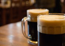 Beer. Two glasses of dark beer on table Royalty Free Stock Photo