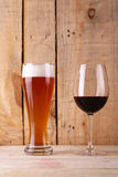 Beer versus wine. Tall glass of light beer and red wine glass over a textured wood background Stock Images