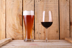 Beer versus wine. Tall glass of light beer and red wine glass over a textured wood background Stock Photography