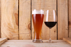 Beer versus wine. Tall glass of light beer and red wine glass over a textured wood background Stock Photo