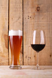 Beer versus wine. Tall glass of light beer and red wine glass over a textured wood background Royalty Free Stock Photos