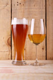 Beer versus wine. Tall glass of light beer and white wine glass over a textured wood background Stock Photos
