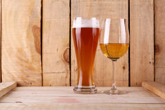 Beer versus wine. Tall glass of light beer and white wine glass over a textured wood background Stock Images