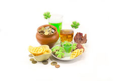 Beer and whiskey and a pot of coins with not many snacks on St. patrick`. Beer a green glass with whiskey and a pot of coins with not many snacks and a pile of stock image