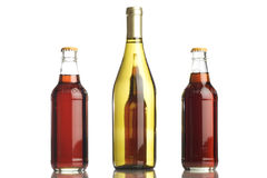 Beer and white wine. Bottles placed together on a reflective tabletop Royalty Free Stock Image