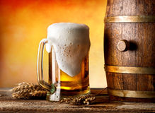 Beer witn wheat. Beer with wheat and barrel on a wooden table Stock Images