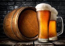 Beer and wooden keg. Near black brick wall Stock Photography