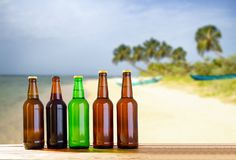 Beer on wooden table on blurred beach background, mock up royalty free stock photo