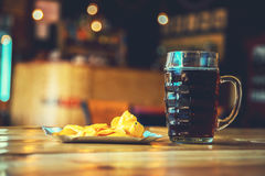 Beer on the wooden table in the pub with free space for your text. A fresh glass of cold dark beer and potato chips on the wooden bar counter in pub with free Royalty Free Stock Image