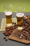 Beer and woods nuts. Board, a nut a splitting, a hammer, glasses, alcohol Stock Photo