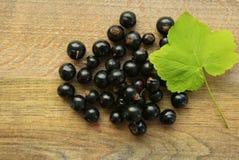 Beere der schwarzen Johannisbeere auf einem Holztisch Lizenzfreie Stockfotografie