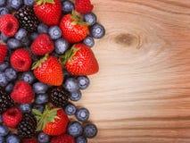 Beeren auf hölzernem Hintergrund. Erdbeeren, Blaubeere lizenzfreies stockbild