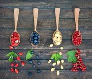 Beeren in den hölzernen Löffeln auf hölzernem Hintergrund Collage von verschiedenen Beeren Wilde rote und gelbe Erdbeere, Blaubee stockfoto