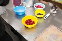 Beeren in den Schüsseln an der Süßigkeitengeschäftsküche lizenzfreie stockfotos