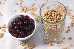 Beeren der reifen Kirsche auf einer weißen Platte und einem Glas Kirschsteinen Stockbilder