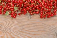 Beeren einer roten Johannisbeere und des Laptops auf der braunen hölzernen Beschaffenheit Lizenzfreies Stockfoto