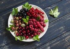 Beeren - Himbeeren, Stachelbeeren, rote Johannisbeeren, Kirschen, Schwarze Johannisbeeren auf einer weißen Platte Lizenzfreies Stockfoto