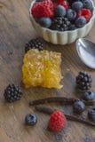 Beeren, Vanilleschote und Bienenwabe auf Holzoberfläche Lizenzfreies Stockbild