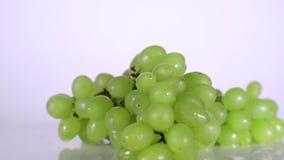 Beeren von gr?nen Trauben in den Wassertropfen, die auf Tabelle sich drehen stock footage