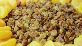 Beeren von Rosinen fallen auf eine Platte, trocknenden Früchte - Rosinen und getrockneten Aprikosen Bestandteile von festlichen T stock video