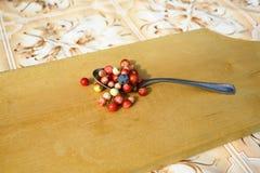 Beerenmoosbeeren und -blaubeeren im Löffel auf Tabelle Stockfotos