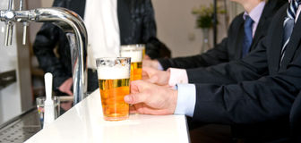 Beers on a Bar. A row of people holding their beers on a bar with a shallow depth of field royalty free stock images