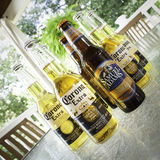 Beers on the Deck. Corona and Samuel Adams Octobrefest beers sit on a glass pato table on an outdoor deck; angle shot; square layout Royalty Free Stock Photos