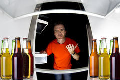 Beers in the Fridge. Man looking inside a fridge with bottles of beers late at night Royalty Free Stock Photos