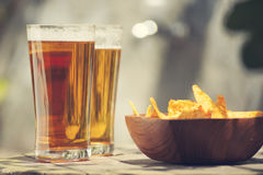 Beers with nachos chips on a wooden table. Two Glasses of beer with nachos chips on a wooden table Stock Photography