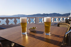 Beers and olives next the sea. Royalty Free Stock Image