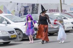 Beersheba, Israël 24 maart, Kinderen met hun moeder in de Carnaval-kostuums van Purim op de straat van de stad Stock Afbeeldingen