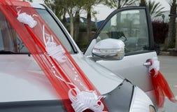 Beersheba, Israël 24 maart, Scharlaken lint met witte organza buigt op een witte het landkruiser van de huwelijksauto Stock Fotografie