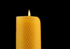 Beeswax Candle. Yellow honeycomb beeswax candle on black stock image