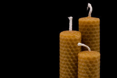 Beeswax candles. Three beeswax candles, tiered, isolated on black with fading light Royalty Free Stock Photography