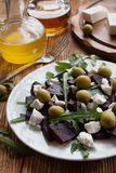 Beet (beetroot) salad with cheese, olives and arugula on the white plate. Olive oil and lemon dressing. On the wooden table Stock Images