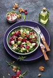 Beet or beetroot salad with fresh arugula, radicchio, soft cheese and walnuts on plate with fork, dressing and spices on blue royalty free stock photos