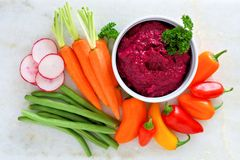 Beet hummus with fresh vegetables, above view on white marble Royalty Free Stock Photography