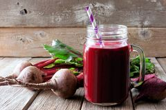 Beet juice in a mason jar with beets over rustic wood royalty free stock photography